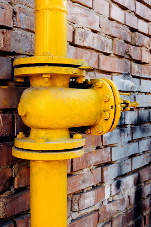 Yellow gas valve over red brick wall. photo