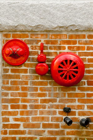 sprinkler alarm: Red fire alarm sprinkler and hidrant in red brick wall.