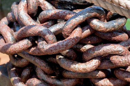 manacle: Rows of rusted chains. Heavy rusted metal chain .