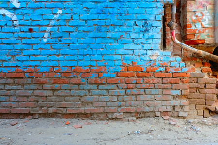 urban decay: Old brick wall half painted in bright blue color and rusty water pipe, a lot of copyspace.