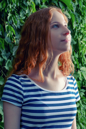 imperturbable: Gorgeous fashionable young woman in striped dress posing looking up. Closeup portrait of trendy redhead girl with natural makeup. Stock Photo