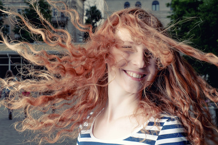 blithe: Red haired girl with flying hair outdoors. Happy casual girl.