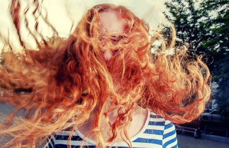 redhead girl: Portrait of a beautiful redhead girl with flying hair in the wind outdoors. Young casual girl with wavy hair