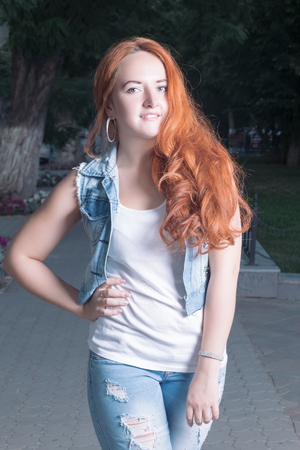 teared: Young red-haired women weared teared jeans outdoors