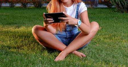 crosslegged: Teen girl issitting crosslegged on spring grass with her digital tablet PC in arms. Young woman enjoying her time in park with tablet computer. Barefeet female. Copyspace. Toned image. Sunset warm light Stock Photo