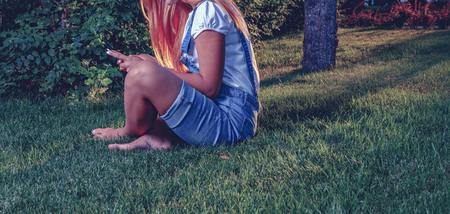 face side: Young woman using tablet outdoor is sitting on grass, no face, side view. Copyspace. A lot of space for text Stock Photo