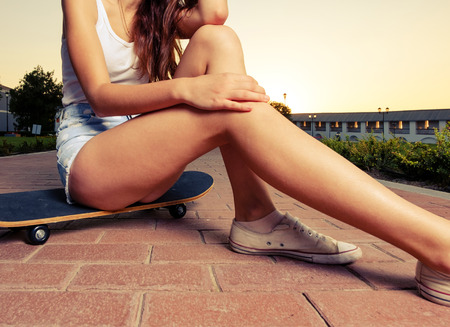 board shorts: Legs of skateboarder girl sit on the board in short jeans shorts place for text is on the ground. Toned color image. Colorized.