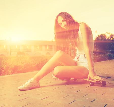 lit image: Color toned image of young girl sitting on her skateboard back lit