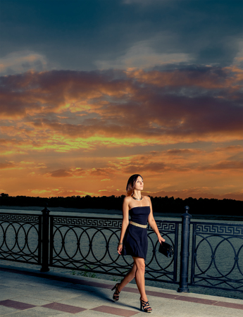 ander: Beautiful woman walking away in  the night.  Fashionable femele in small black dress walking along the embankment with metal fence ander orange sunset sky with clouds