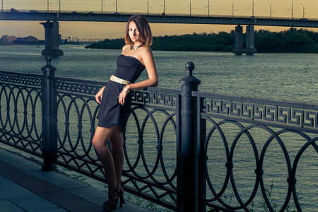leaned: Fashion girl with is leaned back against metal fence of embankment