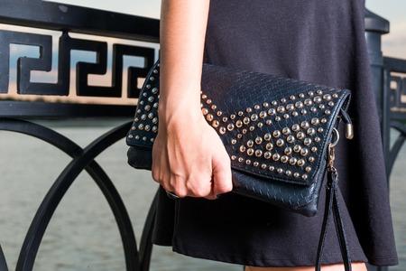 La giovane donna alla moda alla moda con la borsa nera sta posando all'aperto vicino al recinto.