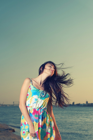 waist up: Waist Up Shot of Young Women on Seaside with wind fluttering her hair. Stock Photo