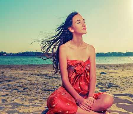 Long haired brunette meditate on sandy beach with flattering hair fly with the wind