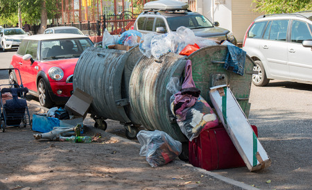 overfilled: Garbage overfilled trash dumpsters in the street, surrounded by expensive cars