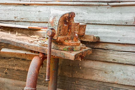 holdfast: Old rusty clumping device on weathered work bench. Stock Photo