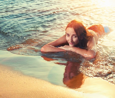 mojado: Joven muchacha adolescente pelirroja tumbada en la playa en la puesta del sol y mirando a ti con la barbilla en sus brazos.