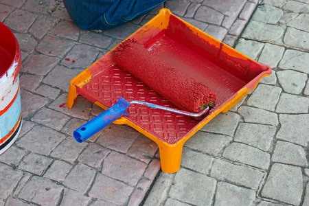 red paint roller: Paint roller (roll) and tub with red color paint