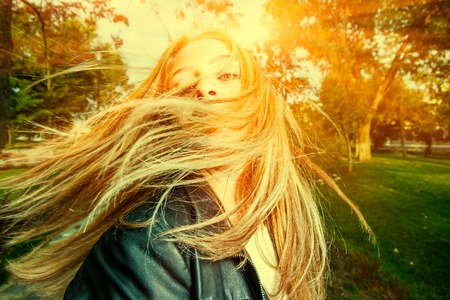 swept: Young woman with wind swept hair backlit , color filtered image, toned instagram color