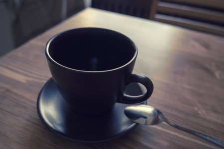 cup: Dark colored cup of coffee in a brown cup on wooden background