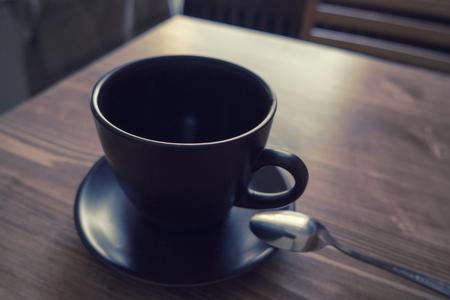 taza: Taza de color oscuro de caf� en una taza de caf� sobre fondo de madera Foto de archivo