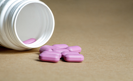 antibiotic pink pill: Violet pills spilled from a bottle on a craft paper background.