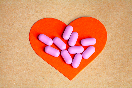 coeur sant�: Heart health concept. Pink Pills on Red Heart on brown craft paper background