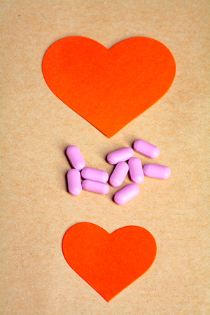 coeur sant�: Two paper hearts and heart pills in the center vertical image. Heart health concept.