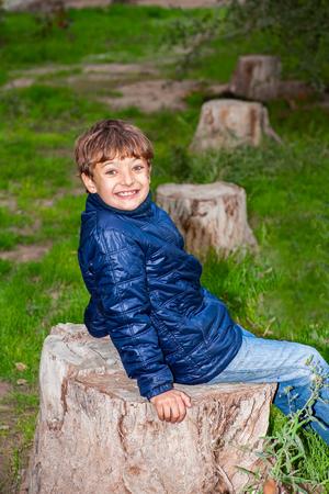 tree stump: Portrait of a cute kid outdoor on a tree stump enjoying nature