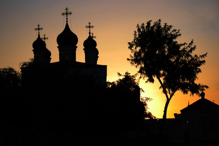 stereotypical: Orthodox church and birch silhouette at sunset, russian stereotypical symols, Astrakhan Russia.