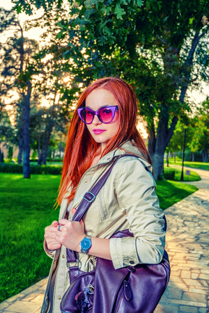 redhair: Redhair woman in casual clothing posing outdoors in 60th fashion  sunglasses and bright violet handbag.