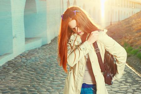 Trendy redhair woman with fashion handbag posing outdoors photo