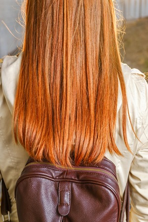 Rear view of redhair teen girl with backpack photo