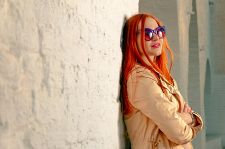 Redhair woman looking away happy. Trendy girl posing near white brick wall in casual clothes and fashionable 60th style sunglasses. A lot of space for text. Instagram color filter imitation. photo
