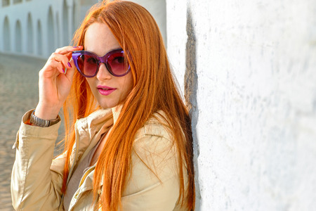 Trendy redhair woman in fashion sunglasses outdoors a lot of copy space on wall photo