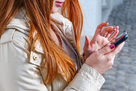 Closeup of redhair girl texting on mobile phone outdoors on old paved street background photo