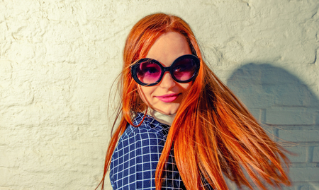 turn about: Trendy carrot-top girl turn around with her hair fly about her. Young woman weared in 60th fashion style sunglasses look back. A lot of copy space on white brick wall. Stock Photo
