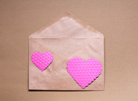 envelop: Two pink hearts on craft paper envelop over brown  background.