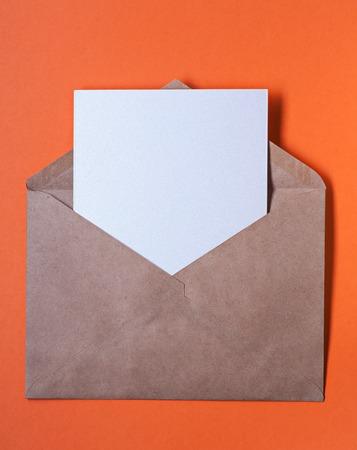 envelop: Brown paper envelop with blank letter inside on orange background Stock Photo