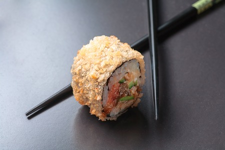 fryed: Fresh sushi with chopsticks over black background with blurred reflection and copy space