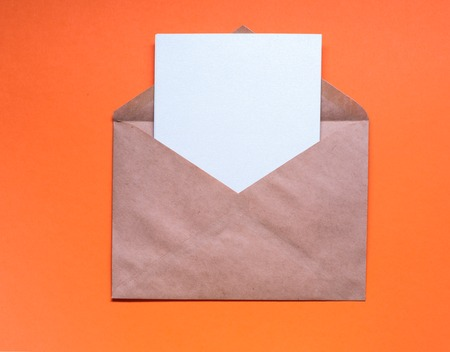 Envelop with blank letter  on orange background. Stock Photo