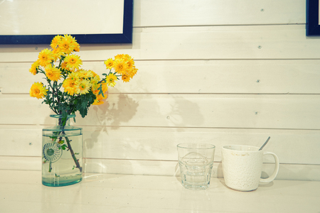 colorized: Yellow spring flowers in vintage glass bottles and two cups on white  barn wall background, cottage interior decoration, copy space, oned image, colorized shot. Stock Photo