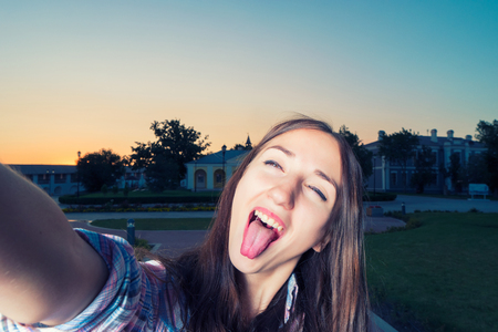tongue out: Young funny girl is making selfie having fun with her tongue is sticking out Stock Photo