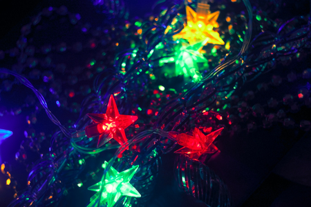 xmass: Blurred Christmas and New Year Decoration. Garland with stars. Holiday Glowing Background. Shallow DOF Stock Photo