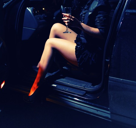Young woman drink vine in her car in the night toned colorized image.