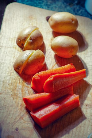 pices: Young potatoes and carrots on wooden  background in pices. Stock Photo
