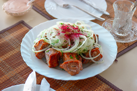 souse: Traditional Turkish Shish Kebab on plate. Grilled meat and onion on top and souse and empty tea glass with spoon Stock Photo