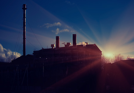 colorized: Silhouette of power plant on evening background of setting sun, toned colorized image. Stock Photo