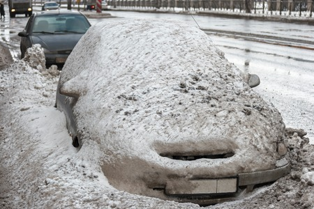 inclement: Car covered with old mad snow. Vehicle covered with snow in the winter blizzard in the street of Saint Petersburg, Russia.