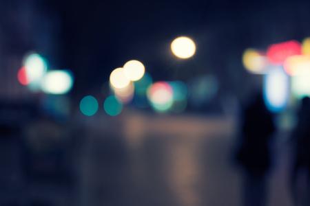 silhouette voiture: Night street défocalisé beau fond sur l'obscurité, beaucoup de copyspace et silhouettes de gens qui marchent Banque d'images