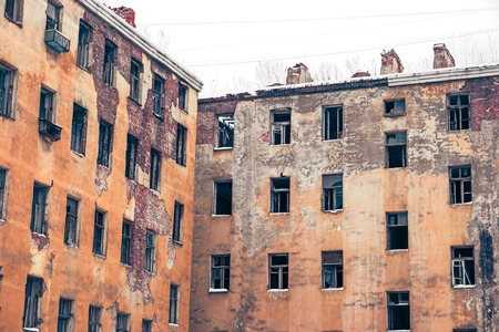 colorized: Old abandoned buildings wall with empty windows toned image, colorized shot.